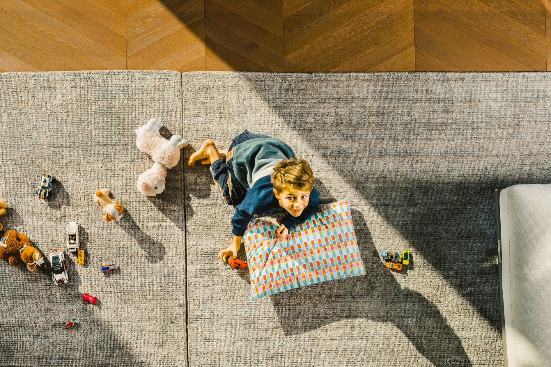Bambino su tappeto con federa cuscino anni 70